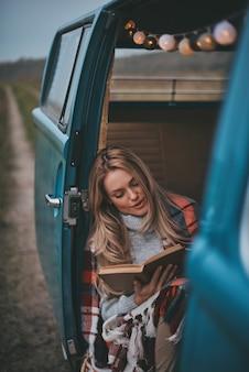 Am lesen beteiligt. attraktive junge frau bedeckt mit decke, die ein buch liest, während sie innerhalb des blauen retro-stil-minivans sitzt