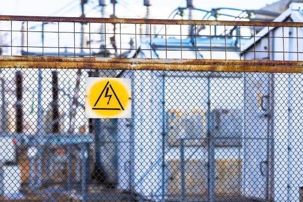 Am maschendrahtzaun, der das umspannwerk der stromleitung umgibt, hängt ein warnschild, das auf die gefahren hoher elektrischer spannung hinweist.