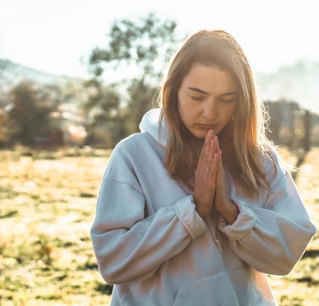 Am morgen schloss das mädchen die augen und betete im freien. die hände waren im gebetskonzept für glauben, spiritualität und religion gefaltet. frieden, hoffnung, träume konzept.