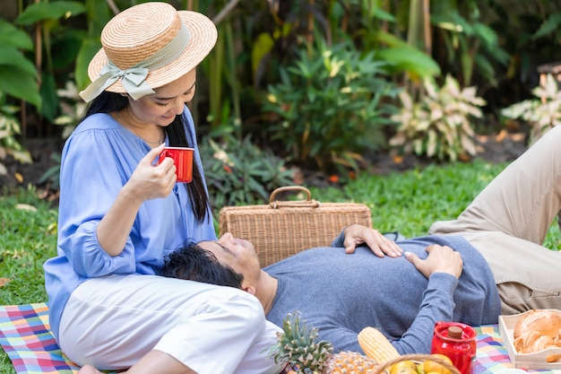 Am morgen. senior asiatisches paar, das kaffee und picknick im park trinkt.