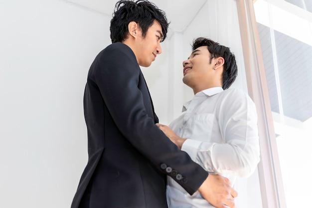 Am morgen süßer moment der liebe. asiatisches homosexuelles paar umarmt ehemann vor der arbeit.