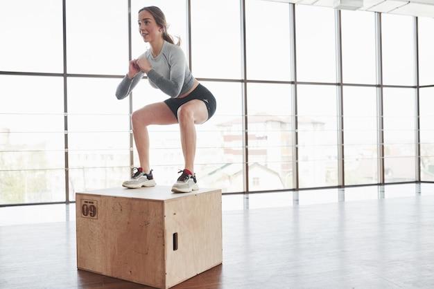 Am rand der box. sportliche junge frau haben fitness-tag im fitnessstudio zur morgenzeit