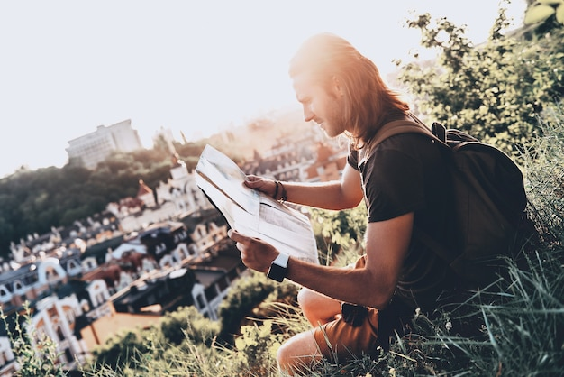 Am richtigen platz. hübscher junger mann in freizeitkleidung mit blick auf die karte