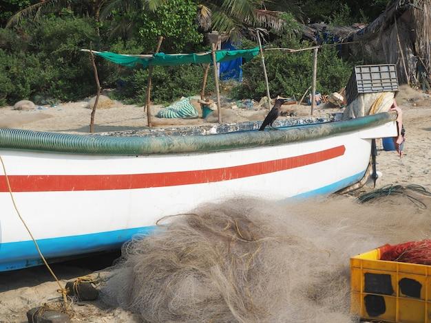 Am sandstrand steht ein buntes fischerboot. daneben sind fischernetze