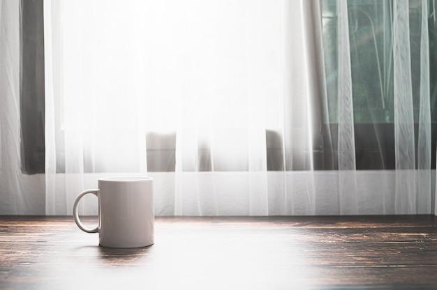 Am schreibtisch stehen ein glas wasser und eine kaffeetasse.
