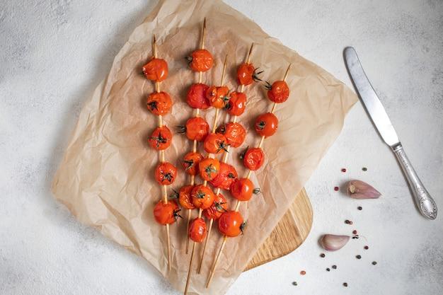 Am spieß gegrillte kirschtomaten auf backpapier legen. mit olivenöl, knoblauch, salz und pfeffer gekocht