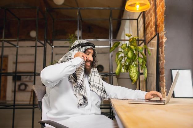 Am telefon arabischer geschäftsmann, der im büro-business-center mit geräte-gadget arbeitet