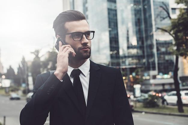 Am telefon. selbstbewusster junger mann im vollen anzug, der am handy spricht