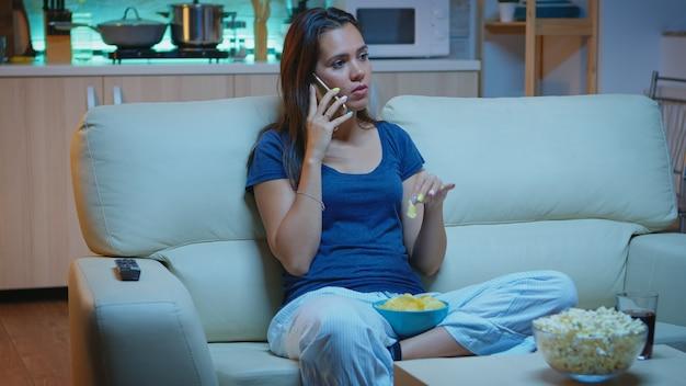 Am telefon sprechen, eine snack-schüssel halten und snacks vor dem fernseher essen. fröhliche, entspannte, einsame dame im pyjama, die den abend auf einer bequemen couch vor dem fernseher mit smartphone genießt