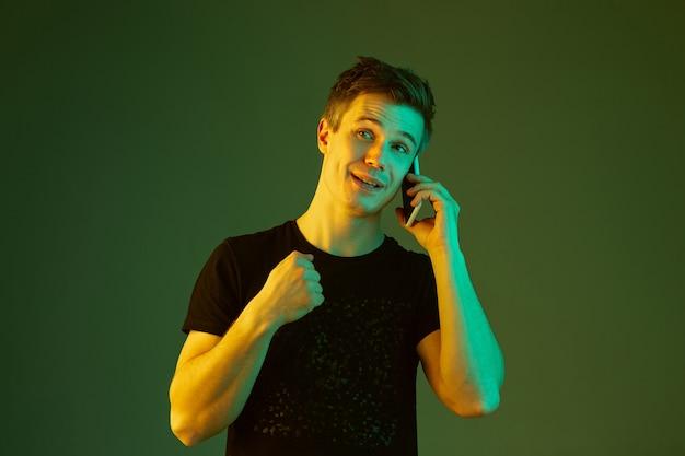 Am telefon sprechen, lächeln. porträt des kaukasischen mannes lokalisiert auf grünem studiohintergrund im neonlicht. schönes männliches modell im schwarzen hemd. konzept der menschlichen emotionen, gesichtsausdruck, verkauf, anzeige.