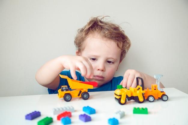 Am tisch saß ein lockiger kleiner junge, der mit plastikwürfeln und autos spielte.