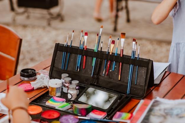 Am tisch stehen kosmetikpinsel zum schminken in einer schwarzen kleinen tasche und farbenfrohe farben