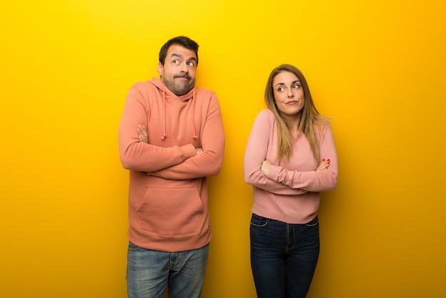 Am valentinstag gruppe von zwei personen auf gelbem grund machen zweifel geste beim anheben der schultern