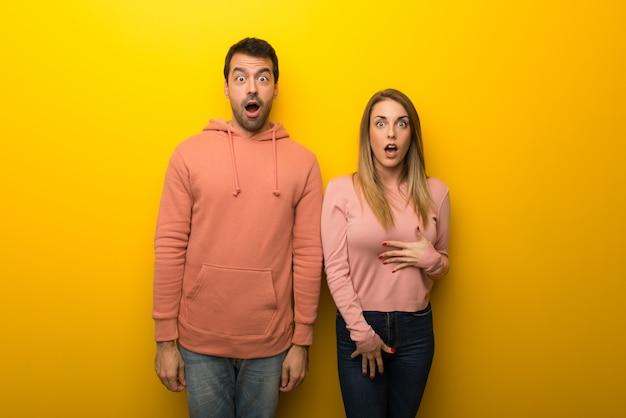Am valentinstag gruppe von zwei personen auf gelbem hintergrund mit überraschung und entsetztem gesichtsausdruck