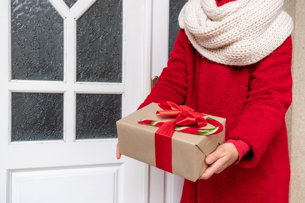 Am vorabend der weihnachtsfeiertage in rotem mantel mit geschenkboxen in der nähe der weißen tür liefern
