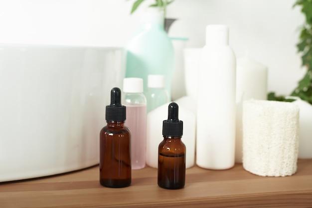Am waschbecken stehen gläser mit feuchtigkeitsspendendem serum, cremes und hautpflegelotionen.