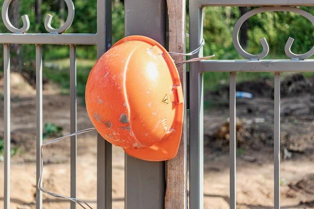 Am zaun hängt ein funktionierender bauhelm. abschlusskonzept. bauherren protestieren gegen niedrige löhne. bauarbeitergewerkschaft - einhaltung der arbeitnehmeranforderungen.