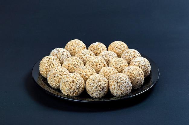 Amaranth ladoo oder rajgira laddu oder cholai ke laddo in schwarzer platte auf schwarzem hintergrund.