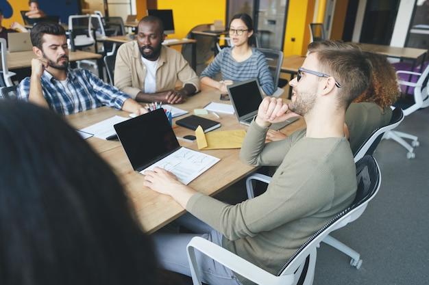 Ambitionierte junge leute kooperieren während der arbeit an einem neuen startup Premium Fotos