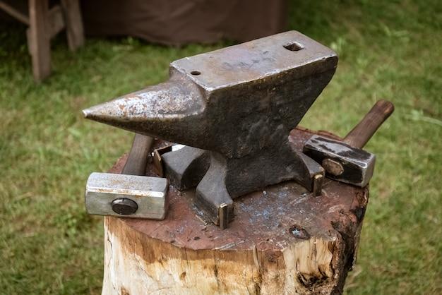 Amboss und hammer auf einem holzklotz in der schmiede