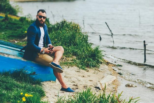 American bearded man sieht in einer blauen jacke am flussufer aus