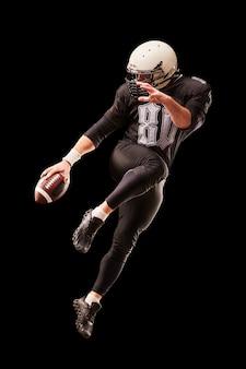 American-football-spieler in einem sprung mit einem ball auf einer schwarzen wand