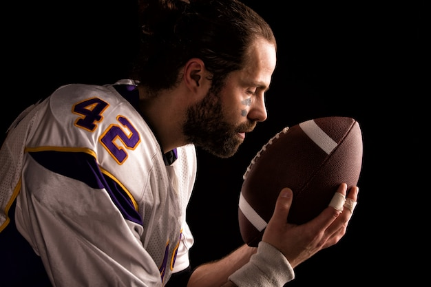 American-football-spieler mit einem ball moment, um vor dem spiel zu beten