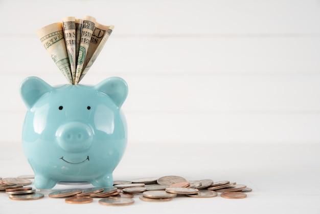 Amerika-dollarbanknotengeld in blaues pastellsparschwein und münzen auf weißem holz