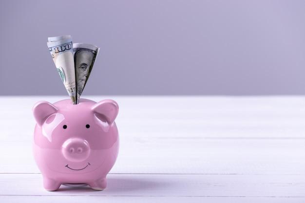 Amerika-dollarbanknotengeld in sparschwein. einsparungsgeldreichtum und finanzkonzept.