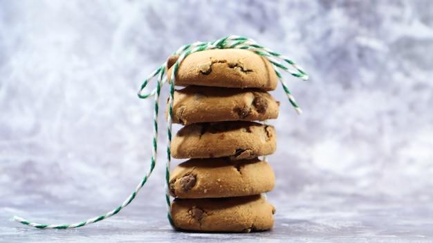 Amerikanische chocolate chip cookies übereinander gestapelt mit grünem faden auf grauem hintergrund. traditioneller abgerundeter knuspriger teig mit schokoladenstückchen. bäckerei. leckeres dessert, gebäck.