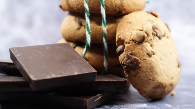 Amerikanische chocolate chip cookies übereinander gestapelt mit grünem faden auf grauem hintergrund. traditioneller abgerundeter knuspriger teig mit schokoladenstückchen. bäckerei. leckeres dessert, gebäck. Premium Fotos