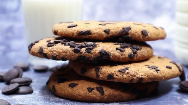 Amerikanische chocolate chip cookies übereinander gestapelt mit milch in einem glas auf grauem hintergrund. traditioneller abgerundeter knuspriger teig mit schokoladenstückchen. bäckerei. leckeres dessert, gebäck.