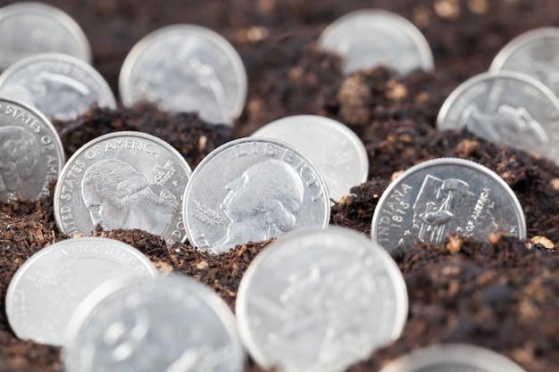 Amerikanische dollar im boden eines landwirtschaftlichen feldes, eines landwirtschaftlichen feldes mit fruchtbarem boden und amerikanischem bargeld