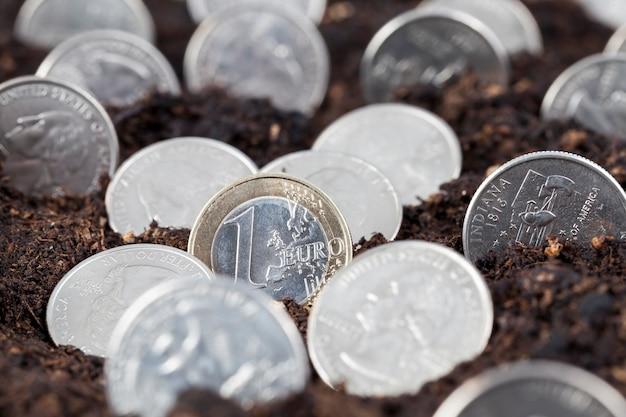 Amerikanische dollar und ein euro im boden eines landwirtschaftlichen feldes, eines landwirtschaftlichen feldes mit fruchtbarem boden und amerikanischem bargeld