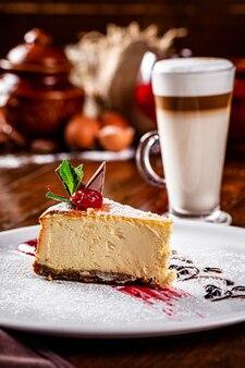 Amerikanische, europäische küche. käsekuchen mit schokolade und kirsche an der spitze. veganes dessert und kaffee latte im restaurant