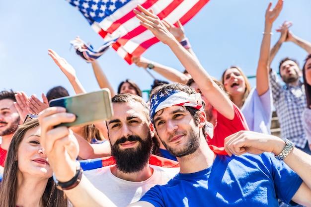 Amerikanische fans, die ein selfie am stadion während eines spiels nehmen