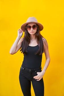 Amerikanische flache junge kaukasische frau mit langer haarsonnenbrille, beigem hut, trägershirt und schwarzer hose, den hut mit einer hand haltend