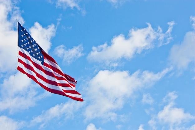 Amerikanische flagge am blauen himmel an einem windigen tag