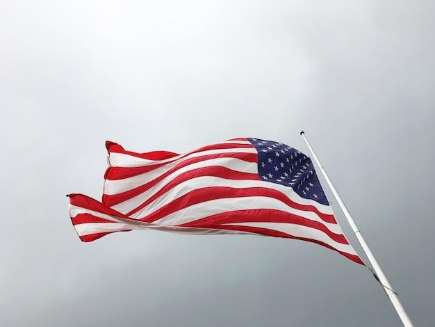 Amerikanische flagge auf dem hintergrund eines düsteren himmels. flagge der vereinigten staaten, die halbmast fliegen.