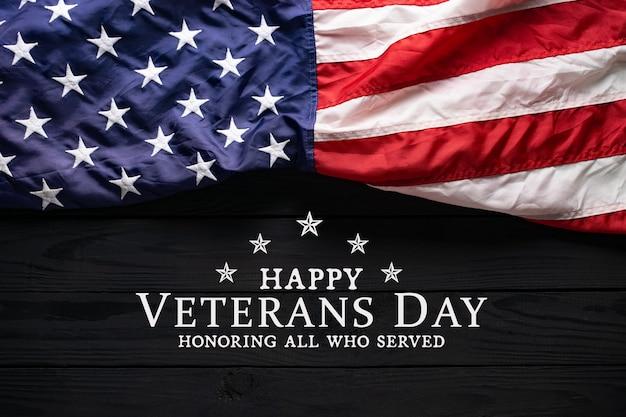 Amerikanische flagge auf schwarzem holz mit text veterans day.