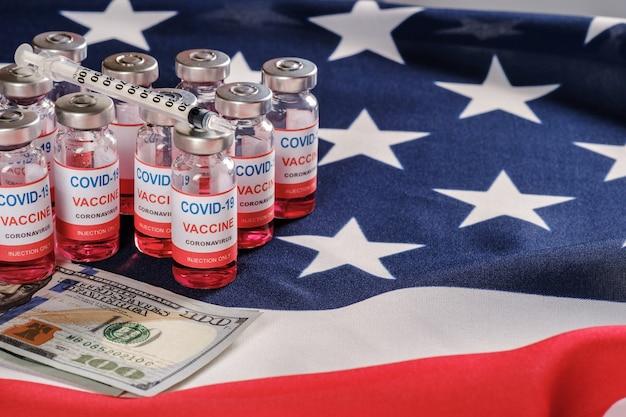 Amerikanische flagge, coronavirus-impfstoffflaschen, spritze und geld