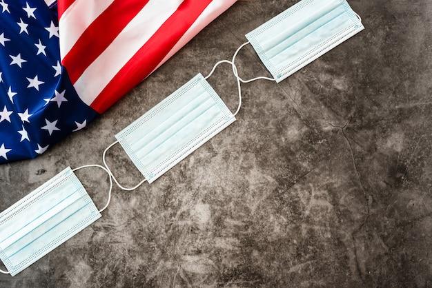 Amerikanische flagge, coronavirus-masken und kopierraum.