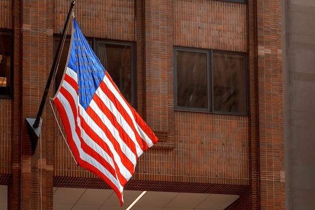 Amerikanische flagge, die auf das gebäude mit wolkenkratzern new york us wellenartig bewegt