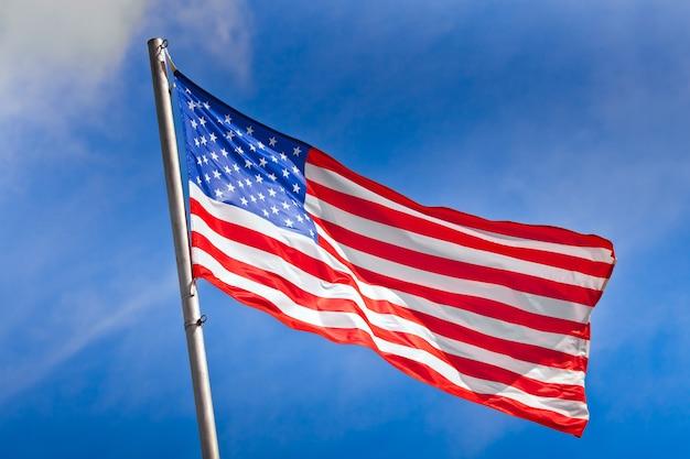 Amerikanische flagge, die gegen den blauen himmel weht