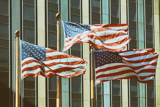 Amerikanische flagge, die vor gebäude new york city vintage-filtereffekte wawing.
