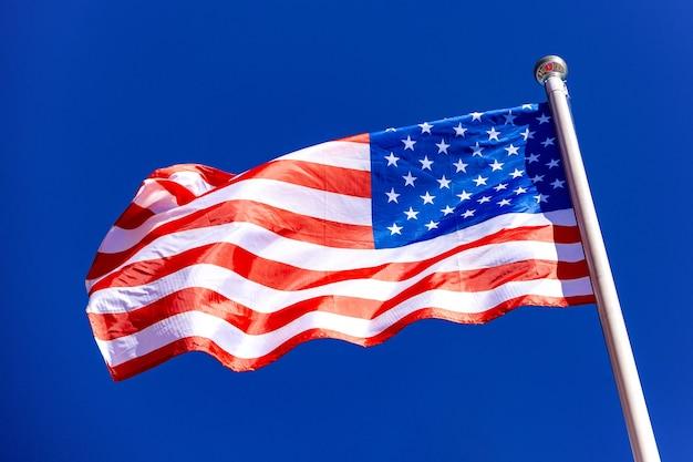 Amerikanische flagge gegen blauen himmel im wind