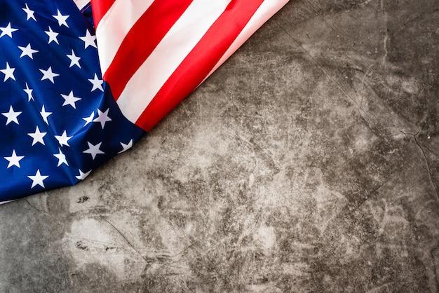 Amerikanische flagge lokalisiert in einer ecke auf einem steingrauen hintergrund.