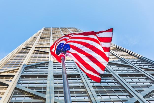 Amerikanische flagge mit modernem wolkenkratzer