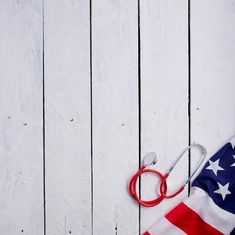 Amerikanische flagge mit stethoskop auf tisch