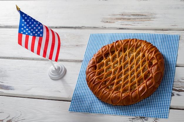 Amerikanische flagge neben rundem kuchen. torte, serviette und kleine flagge. traditioneller kuchen serviert im café. neues gericht in der speisekarte.